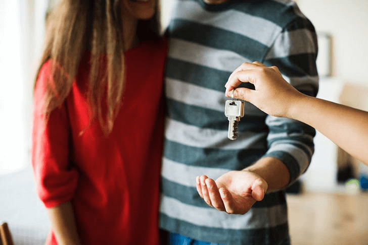 Person giving keys to a couple